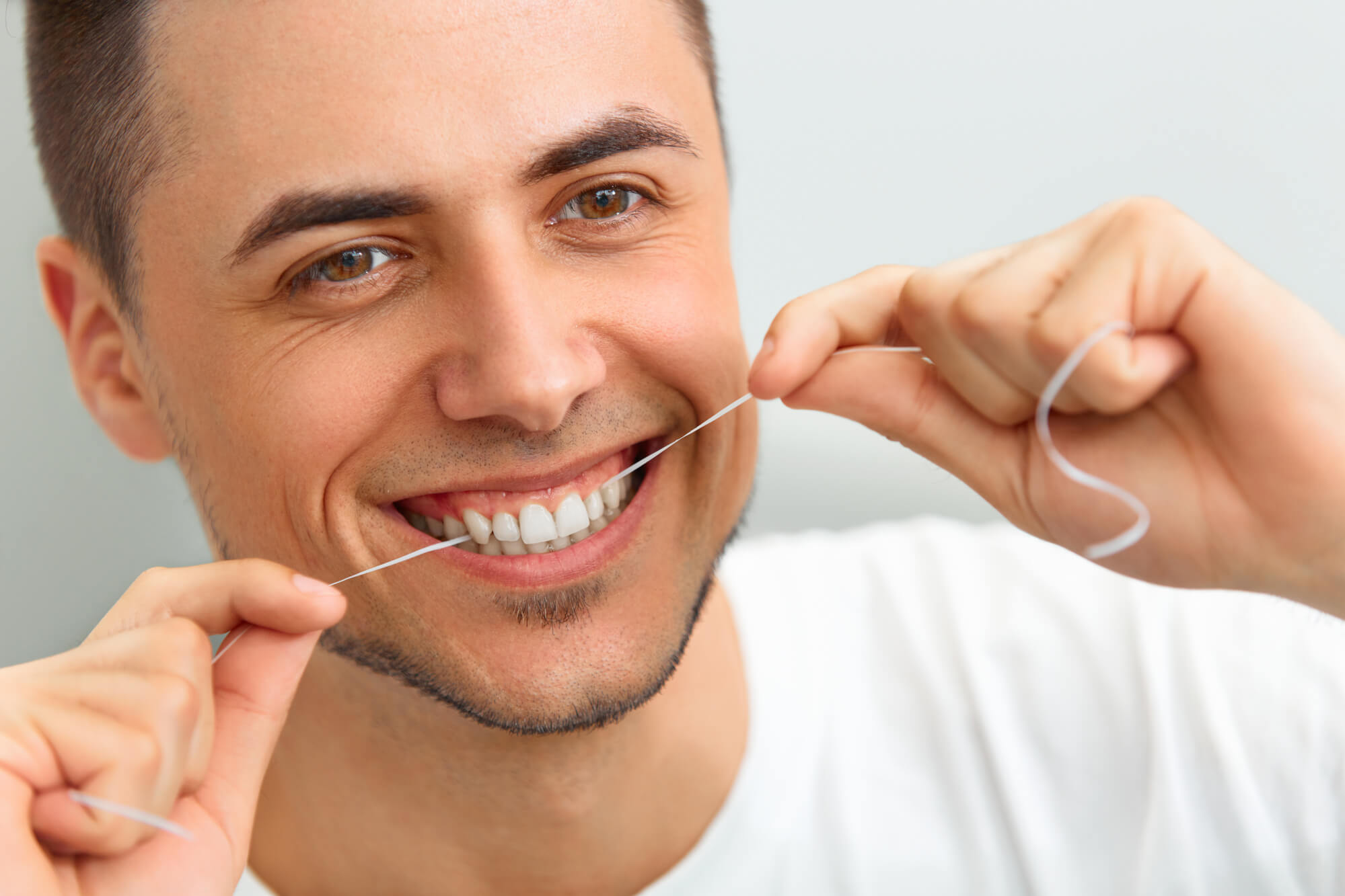 Man flossing after getting a Tooth Replacement in Palm Beach Gardens