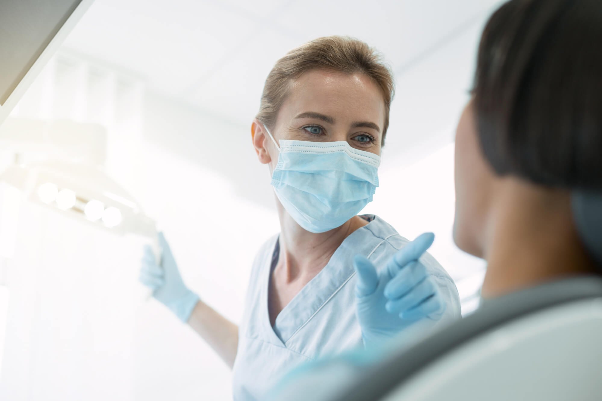 Patient asking dentist answering about Holistic Implants in Palm Beach Gardens
